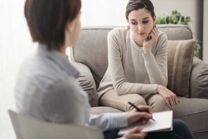 woman looking sad talking with therapist in rehab admissions